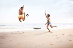 Young mixed race couple playing with football. On beach Royalty Free Stock Image