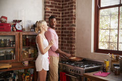 Young mixed race couple preparing breakfast together Stock Photo