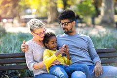 Young mixed race couple spending time with their daughter. Happy young mixed race couple spending time with their daughter stock image