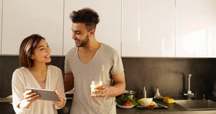 Young Mixed Race Couple Using Tablet Computer Morning Sunlight, Happy Hispanic Man Asian Woman Together In Kitchen stock footage