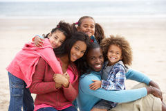 Young mixed race family embracing on beach. Smiling at camera Stock Photos