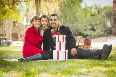 Young Mixed Race Family Enjoying Christmas Gifts in the Park Together Royalty Free Stock Photography