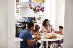 Young African American  family having a birthday meal together at the table in their kitchen, seen from doorway. Young mixed race family having a birthday meal stock photography