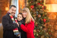 Young Mixed Race Family Portrait In Front of Christmas Tree Indoors. royalty free stock image