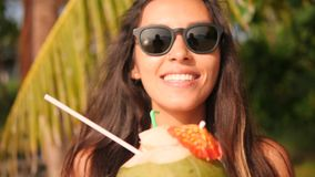 Young Mixed Race Girl Drinking Fresh Thai Coconut Water Cocktail at Tropical Beach. 4K. Phuket, Thailand. Young Mixed Race Girl Drinking Fresh Thai Coconut stock video