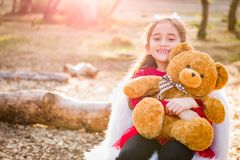 Young Mixed Race Girl Hugging Teddy Bear Outdoors. Cute Young Mixed Race Girl Hugging Teddy Bear Outdoors royalty free stock photo