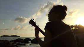 Young mixed race girl playing the ukulele on the beach rocks. Colorful sunset. HD back view silhuette. Thailand. stock video