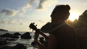 Young mixed race girl playing the ukulele on the beach rocks. Colorful sunset. HD back view silhuette. Thailand. stock footage