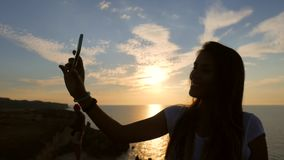 Young mixed race girl taking selfie photo using mobile phone during beautiful sunset on background. HD slowmotion. stock footage