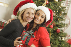 Young Mixed Race Girlfriends with Christmas Gift Stock Image