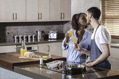Young mixed race happy couple preparing breakfast in the kitchen cooking Royalty Free Stock Images