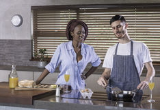 Young mixed race happy couple preparing breakfast in the kitchen cooking Stock Photography