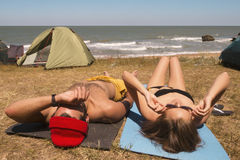 Young Mixed Race Hipster Couple Sunbathing on the Beach near Camping with Tents. Lifestyle Carefree Travel Concept Stock Photography