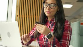 Young mixed race hipster woman holding credit card and using laptop computer stock footage