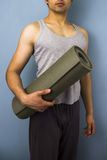 Young mixed race man carrying yoga mat. Slender athletic young mixed race man carrying yoga mat Stock Images