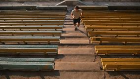 Young mixed race man runner in sport clothes running climbing up stairs in the stadium stock video