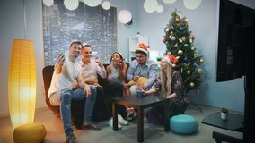 Young mixed race people in Santa hats making video call by smartphone on Christmas party. While blowing party whistle, making cheers and having fun together stock video footage