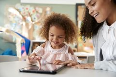 Young mixed race schoolgirl using a tablet computer with a female infant school teacher, working one on one together in a classroo. M, close up stock photos