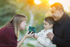 Young Mixed Race Son Handing Christmas Gift to His Mom. Happy Young Mixed Race Son Handing Gift to His Mom As Father Stands Behind royalty free stock photo