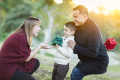 Young Mixed Race Son Handing Gift to His Mom. Happy Young Mixed Race Son Handing Gift to His Mom As Father Stands Behind royalty free stock images
