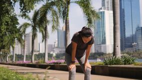 Young Mixed Race Sport Fitness Girl Running in City Park and Using Smart Fitness Tracker Watch Gadget for Cardio Workout. 4K, Slowmotion. Bangkok, Thailand stock video footage