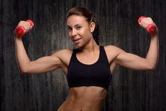 Young mixed race sporty woman holding dumbbells Stock Photography