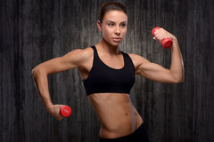 Young mixed race sporty woman holding dumbbells Stock Photo