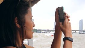 Young Mixed Race Tourist Girl Cruising on Small Thai Boat and Taking Photos Using Mobile Phone. Bangkok, Thailand. 4K