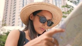 Young Mixed Race Tourist Girl Looking in City Map. Attractive Hipster Girl in Straw Hat and Sunglasses Exploring New. Place. 4K stock video footage