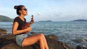 Young mixed race tourist girl playing ukulele on the beach sunset. HD. Thailand, Phuket. stock video