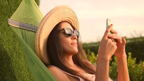 Young Mixed Race Tourist Girl in Sunglasses and Straw Hat Using Mobile Phone in Hammock in Park at Natural Sunset. Lighting. Phuket, Thailand. 4K, Slowmotion stock video
