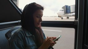 Young Mixed Race Tourist Woman in Bus Using Mobile Smart Phone at Airport. 4K. Young Mixed Race Tourist Woman in Bus Using Mobile Smart Phone at Airport stock footage