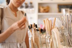 Young Mixed Race Woman Choosing Bamboo Eco Friendly Biodegradable Toothbrush in Zero Waste Shop. No plastic Conscious Minimalism. Vegan Lifestyle. Reduce Reuse royalty free stock image