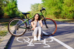 Young mixed race woman cyclist with mountain bike in the forest cycling workout outdoor. Royalty Free Stock Photo