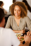 Young mixed-race woman with her boyfriend. Young mixed-race woman holding hands with her boyfriend in a restaurant Royalty Free Stock Photography