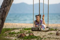 Young mixed race woman lies on the swings on the sea beach. Relax. Young mixed race woman lies on the swings on the sea beach Stock Image