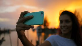 Young mixed race woman making selfie at beautiful sunset. girl silhuette using mobile phone. hd slowmotion. Thailand. stock footage