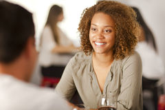 Young mixed-race woman in a restaurant. Happy young mixed-race woman smiling at her partner in a restaurant Royalty Free Stock Photography