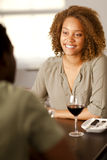 Young mixed-race woman in a restaurant. Happy young mixed-race woman smiling at her partner in a restaurant Stock Photography