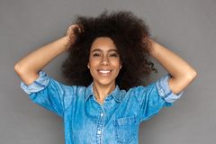 Freestyle. Mulatto woman standing on grey touching hair laughing cheerful close-up royalty free stock photography