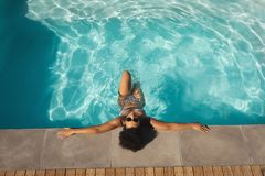 Young mixed-race woman with sunglasses leaning on edge of pool. High angle view of young mixed-race woman with sunglasses leaning on edge of pool in backyard of royalty free stock images