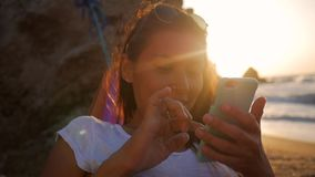 Young mixed race woman texting on mobile phone in hammock at the beach near the sea against stunning golden sunset and. Lens flare. Crimea, Russia. HD stock video