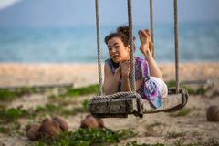 Young mixed race woman on the wooden swings on sea beach. Travel Royalty Free Stock Photos