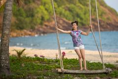 Young woman on the wooden swings on sea beach. Young mixed race woman on the wooden swings on sea beach Stock Photography