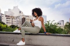 Young mixed woman with afro hairstyle sitting and using cell phone. Full length body. Urban background during summer period, royalty free stock photos