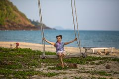Young mixwoman on the wooden swings on sea beach. Young mixed race woman on the wooden swings on sea beach Royalty Free Stock Image