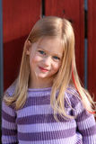 Young model. Young girl leans against a red fence to model her new sweater Royalty Free Stock Photo