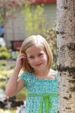 Young Model. 5 year old girl brushes her hair back from her face as she models a summery dress Royalty Free Stock Photos