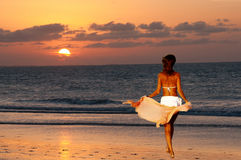 Young model in the beach at sunset. Young bronzed model is going in the sea at sunset Royalty Free Stock Photography
