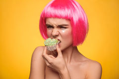 Young model biting cupcake. Young model in pink wig biting small cupcake stock photography